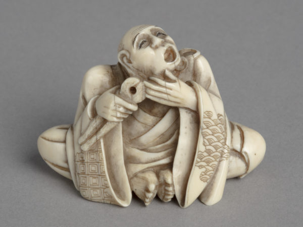 A Japanese ivory netsuke of a man in robes seated with feet together holding pliers to his mouth.