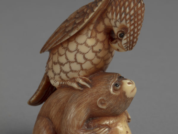 A Japanese ivory netsuke of a hawk perched on the back of a monkey that is crouching over a rock.