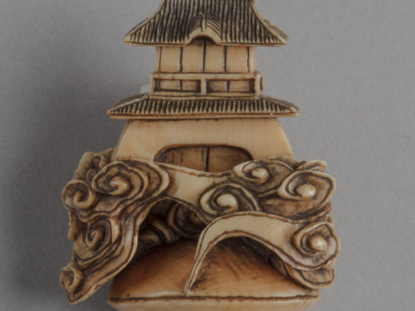 A Japanese ivory netsuke of a two-roofed gate-tower rising out of clouds emerging from a closed clam shell.