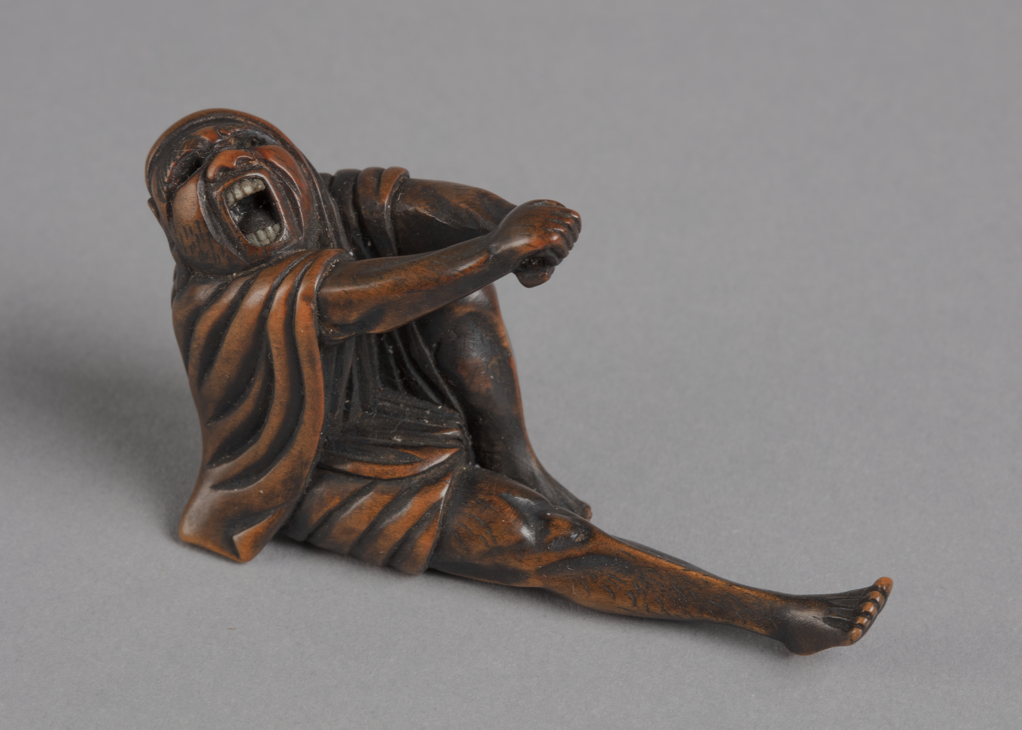A Japanese boxwood netsuke of the monk Daruma yawning, stretching out clasped hands and right leg.