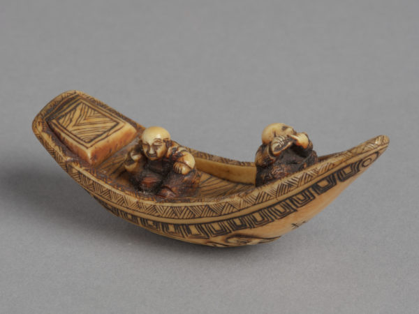 A Japanese ivory netsuke of two seated men, one playing a flute, in a long wooden boat with waves underneath.