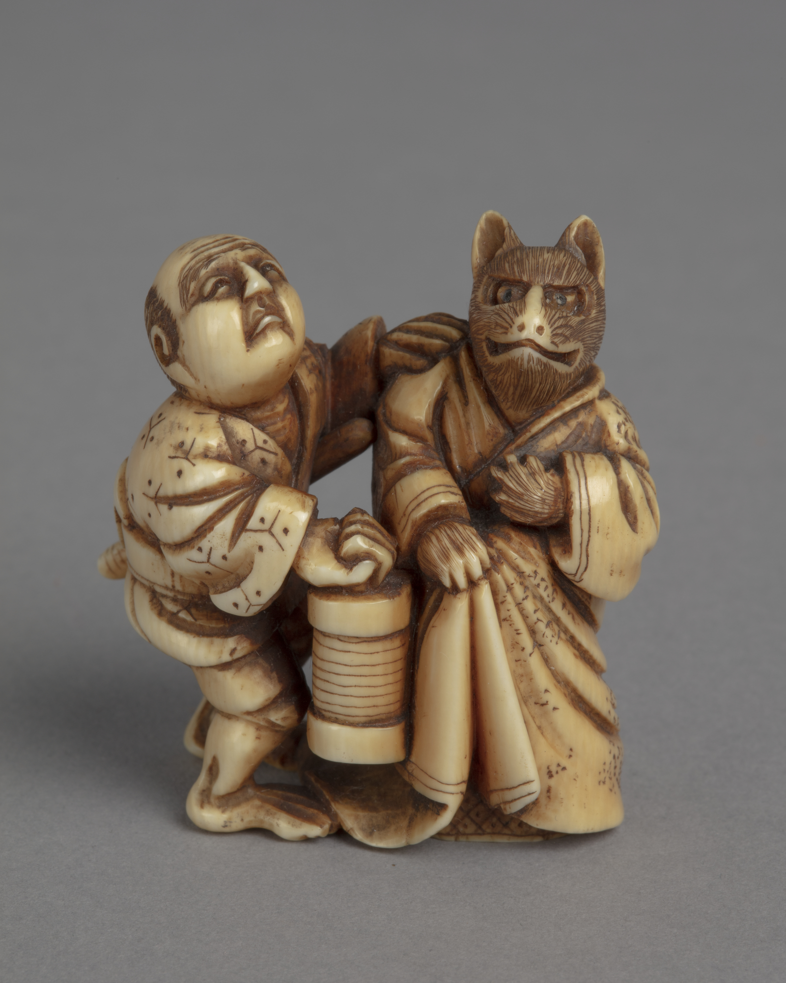 A Japanese ivory netsuke of a kitsune fox dressed in a kimono standing to the left of a man who carries a lantern.