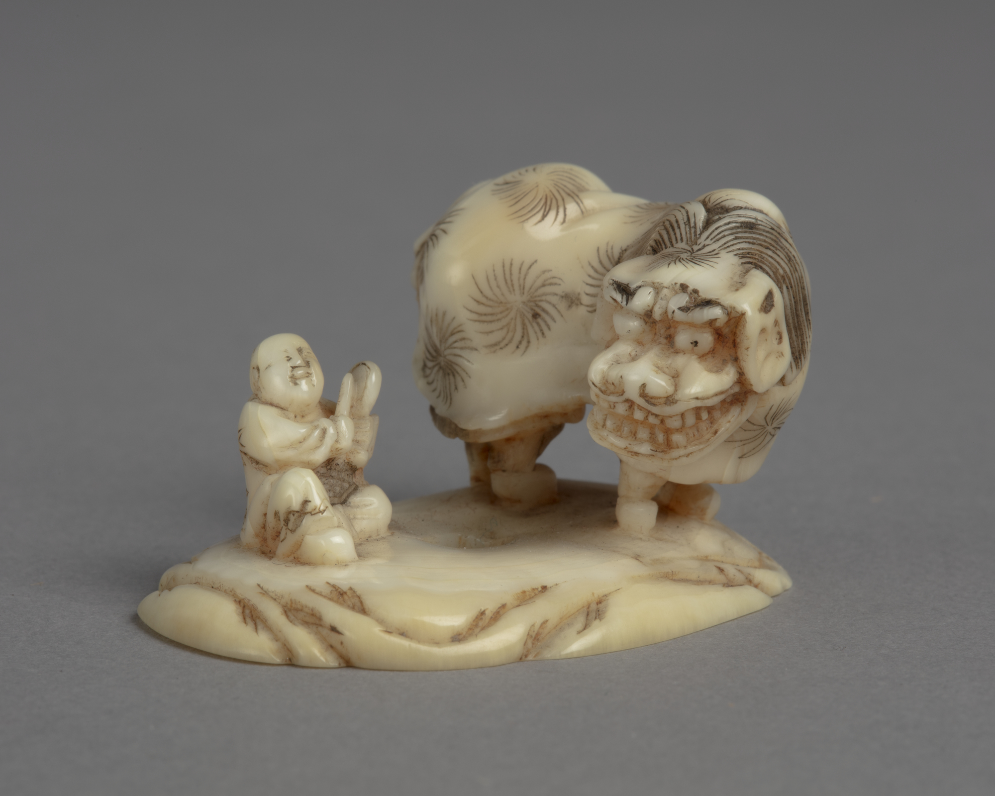 A Japanese ivory okimono ornament of two boys performing lion dance, another seated boy drumming.