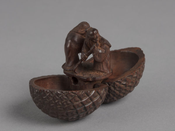 A Japanese boxwood netsuke of a pinecone which opens vertically to reveal a small man and woman standing inside.