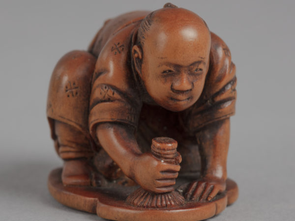 A Japanese boxwood netsuke of a man on his hands and knees polishing the floor with a brush, forming a swirling pattern.