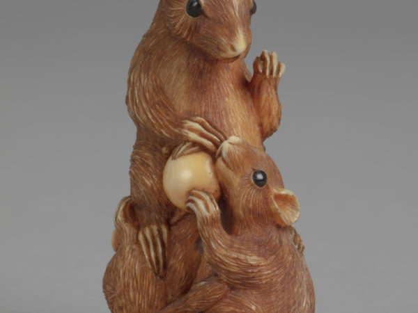 A Japanese ivory netsuke of a recumbent deer with its head turned back along the left side of its body. Eyes inlay with jet. 125 characters A Japanese netsuke of three rats with grapes. The central rat is bigger than the two by its feet.