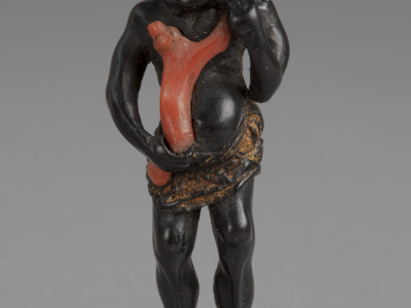 A Japanese ebony netsuke of a Black man wearing a gold loincloth holding a large branch of coral to his chest.