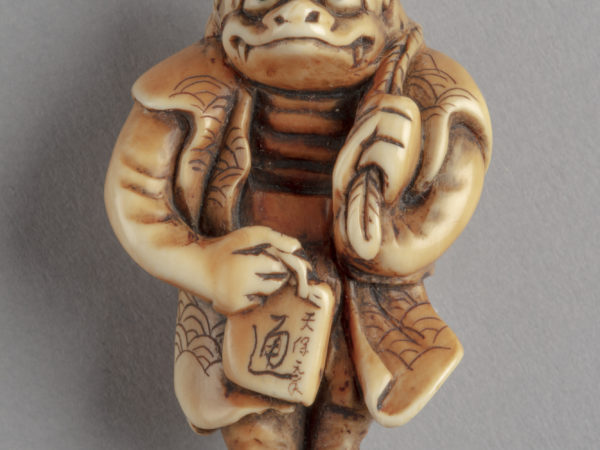 A Japanese ivory netsuke of a kappa, a goblin-like mythical creature. It carries a sake flask slung over its left shoulder.