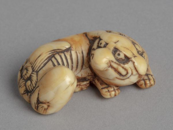 A Japanese ivory netsuke of a baku, a mythical creature with an elephant trunk, rhinoceros eyes, an ox tail and tiger feet.