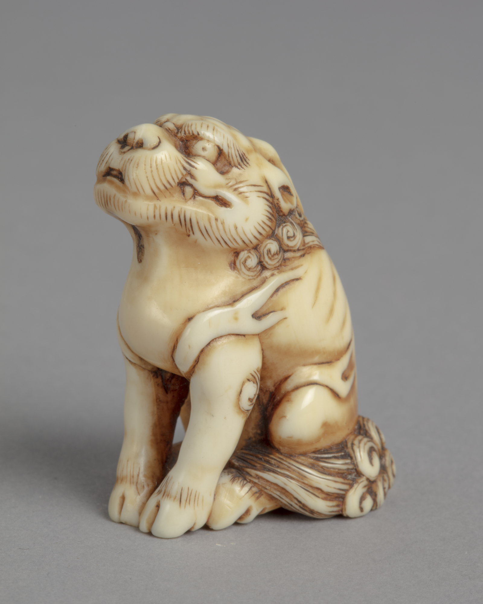 A Japanese ivory netsuke of a seated kirin, a mythical creature that is part dragon, deer, horse, and lion.