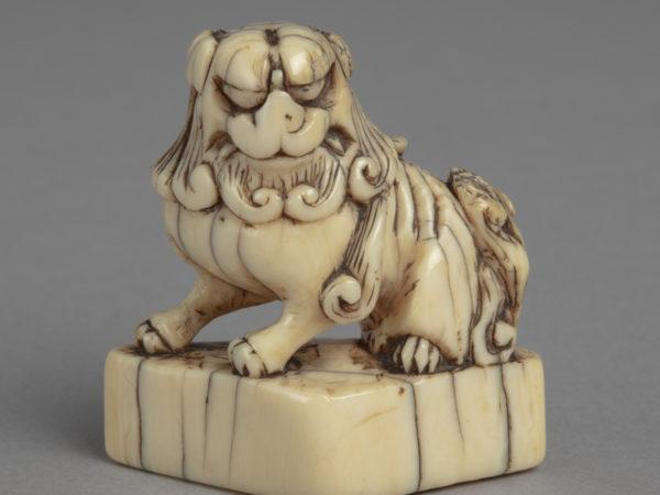 A Japanese ivory netsuke of a Chinese Buddhist lion, seated on a triangular plinth.