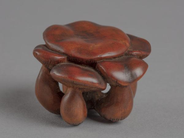 A Japanese boxwood netsuke of a clump of four plump mushrooms.