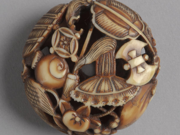 A Japanese ivory netsuke. Carved in openwork are the myriad treasures belonging to the Seven Gods of Good Luck.