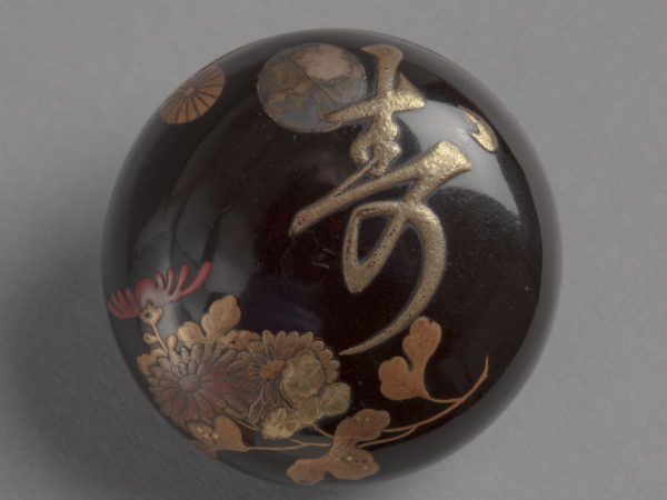 A black lacquer round netsuke with red and gold chrysanthemums and the Japanese word for 'long-life' or 'best wishes'.