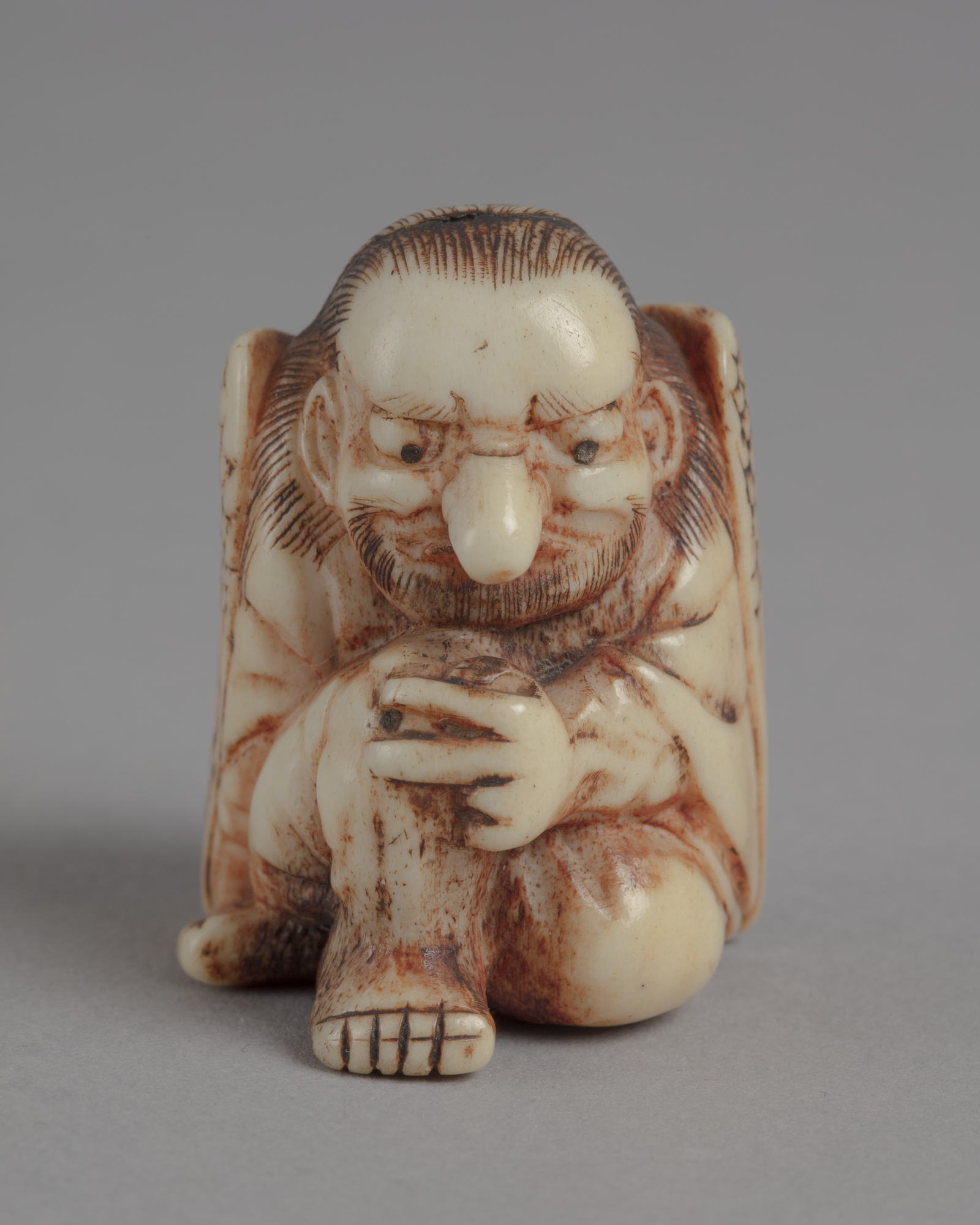 A Japanese ivory netsuke of a seated tengu. It has the body of a man, the wings of a bird, a beard and a long nose.