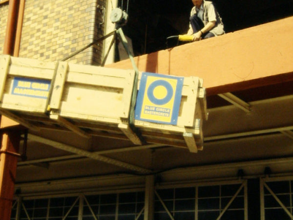 a crane lift a large crate containing the pliosaurus fossil onto the 1st floor of a building, where a man waits