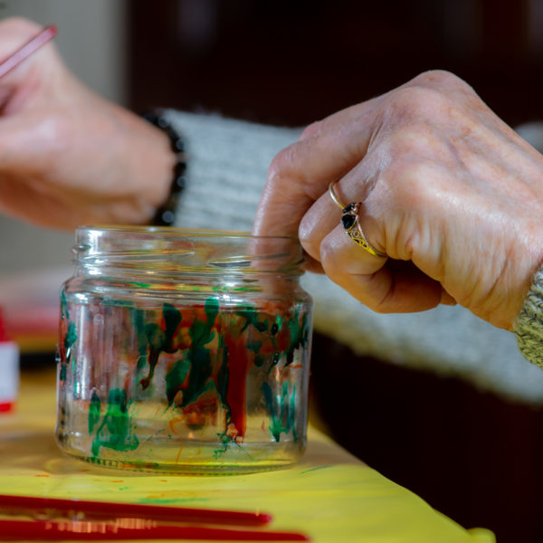 Photo of hands painting a glass jar