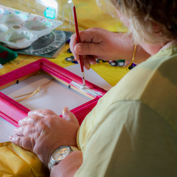Woman painting a picture frame in community art class