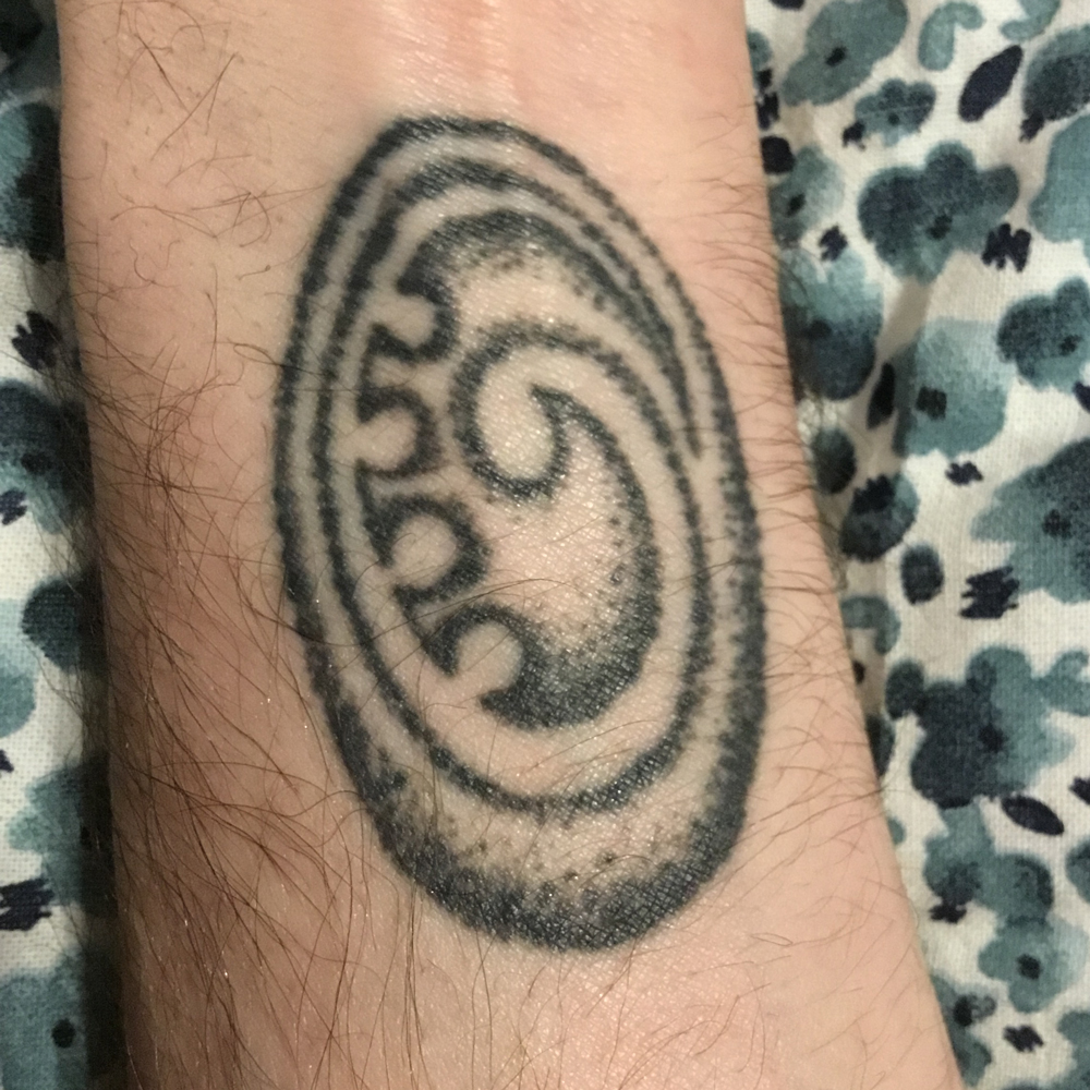 a tattoo on a forearm or a koru, a new zealand symbol meaning 'the inner journey'