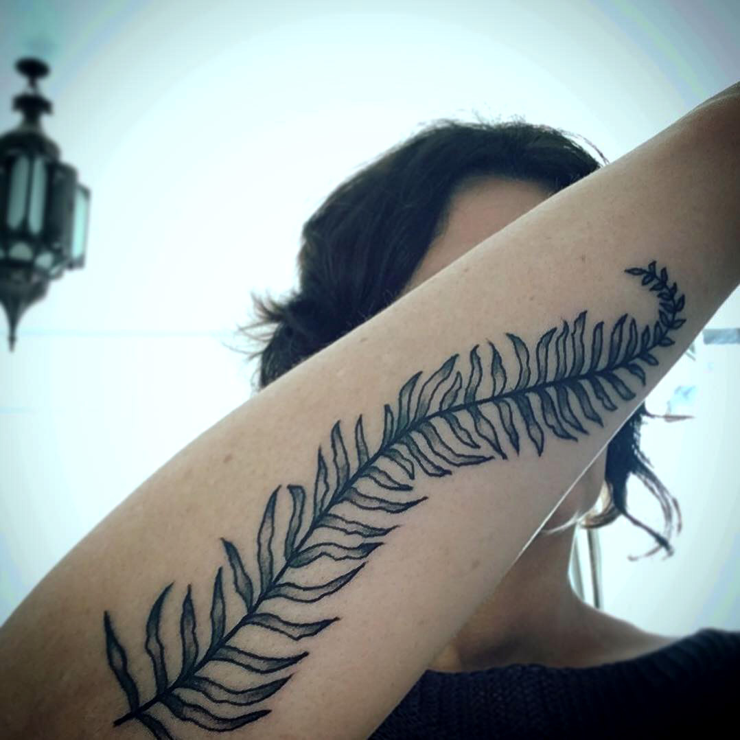 Lady holding up her arm to show a fern a black fern tattoo that runs up her forearm