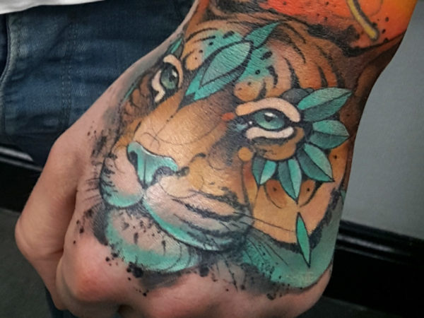 A tiger tattoo on a mans hand, it has bright blue embellishments on its forehead, eyes and mouth