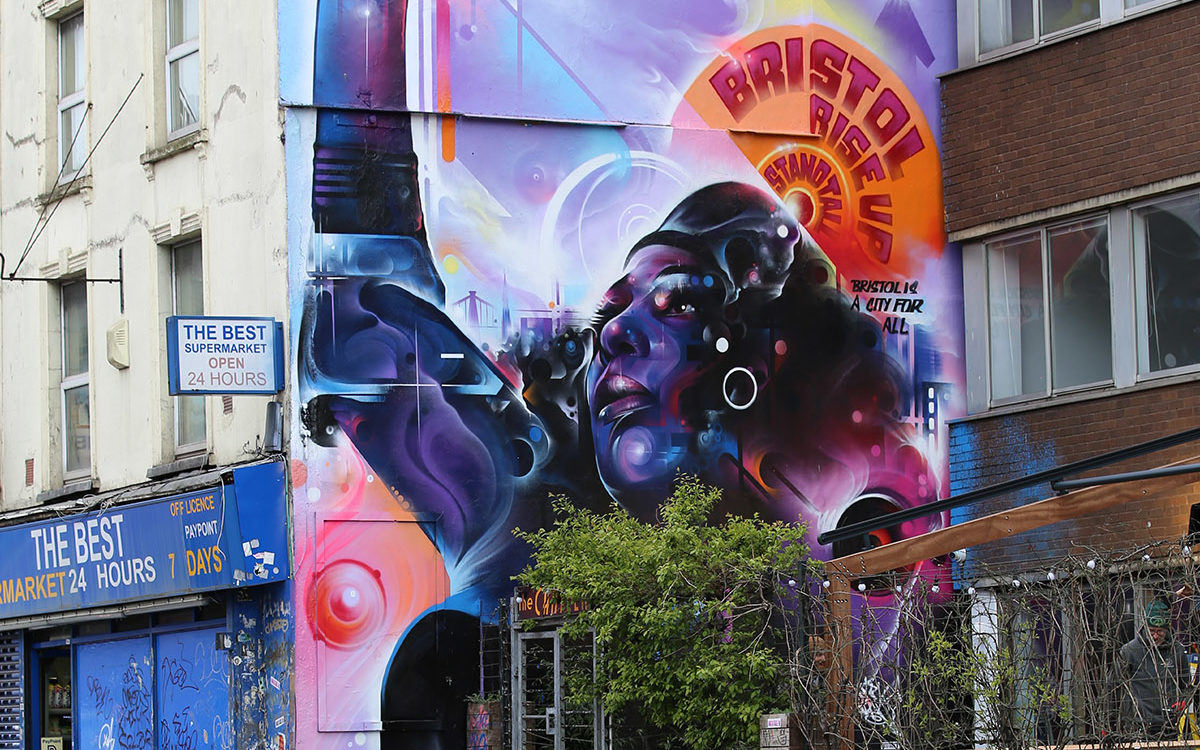 Photo of large scale graffiti on the side of a building. Painting is of a woman with a raised right fist. She wears a beret. 'BRISTOL RISE UP STAND TALL' is written above her head. Painted in purples, blues and pinks. Empty cycle racks are in the foreground.