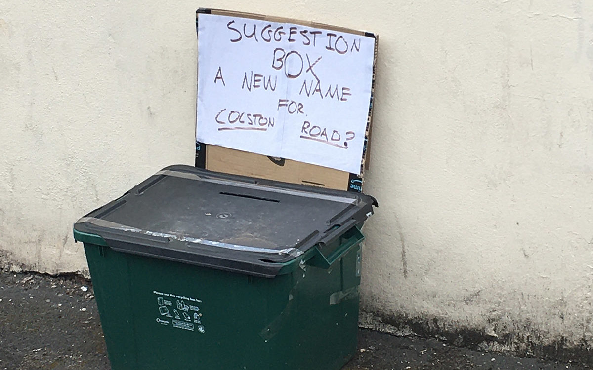 Black recycling box on a pavement. A cardboard sign on the box says 'Suggestion box- a new name for Colston Road?' Above it, the street name has been taped over with blue tape.