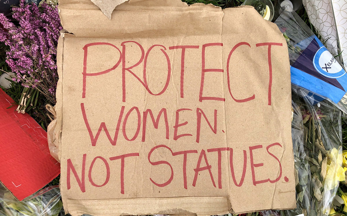 Cardboard protest placards on grass, with flower tributes. Main placard reads 'Protect women not statues'.