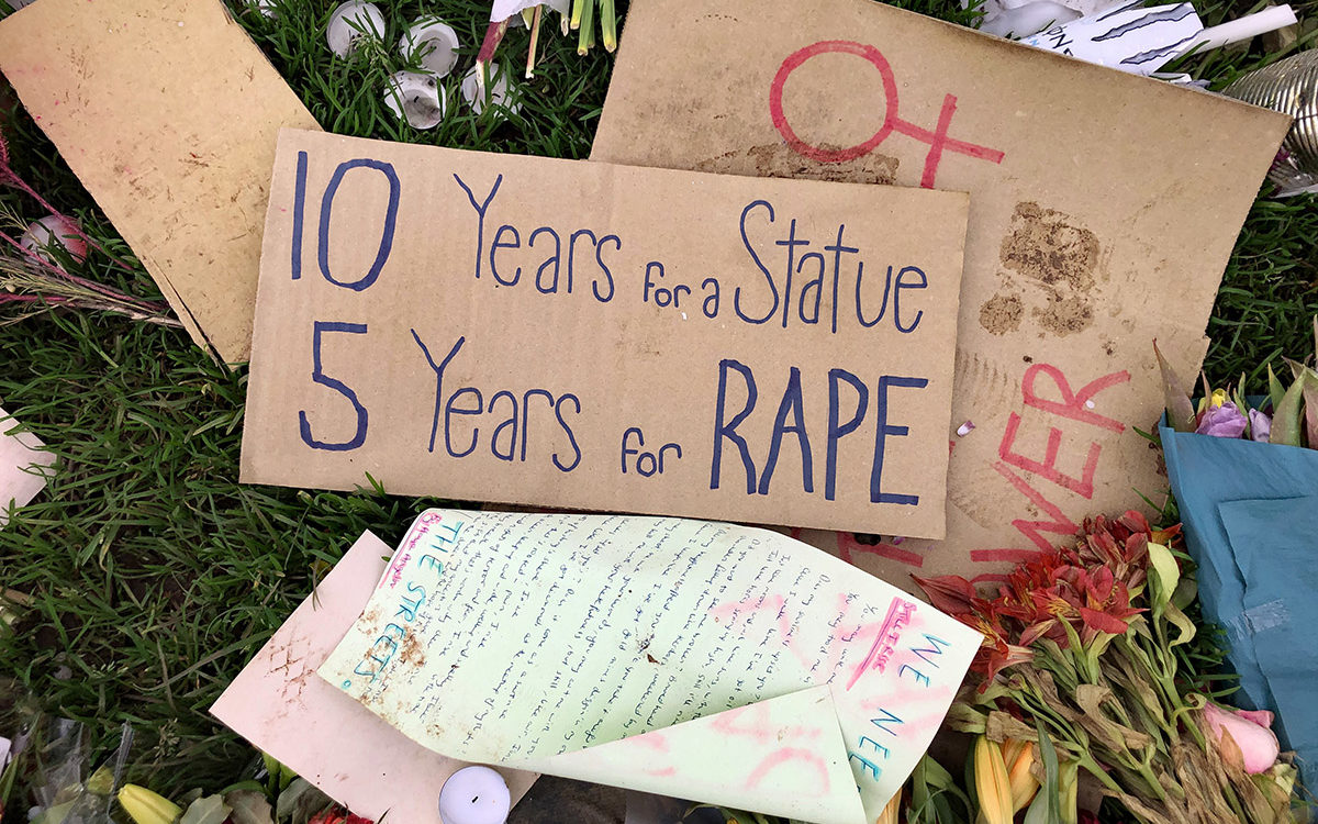 Cardboard protest placards on the ground, with candles and flowers. Main placard reads '10 years for a statue, 5 years for a rape'.