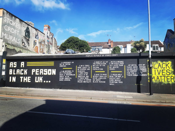 Large painted wall on a sunny day. The wall is painted with a black background with white writing, and yellow lines. Writing states 'As a black person in the UK….' 'Black Lives Matter' is painted at the other end.