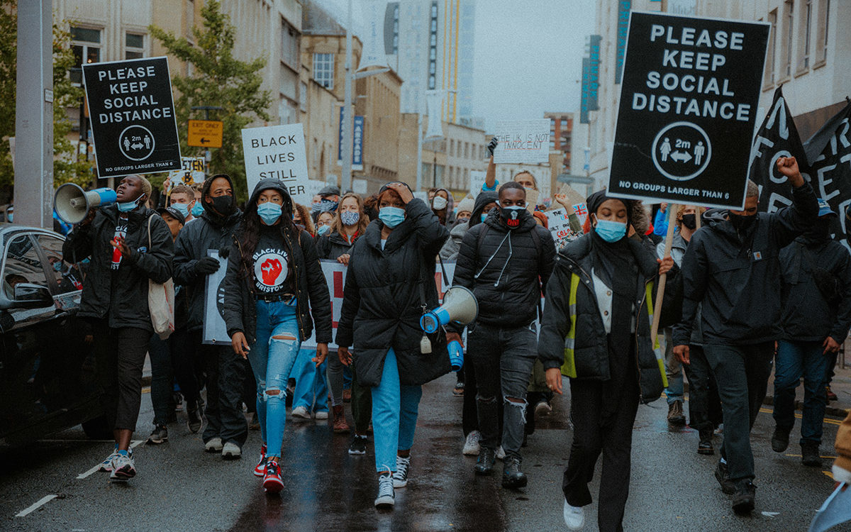 Protest march in central Bristol. Placards read 'PLEASE KEEP SOCIAL DISTANCE' and 'BLACK LIVES STILL MATTER'. A Black woman on the left of the photo holds a megaphone to her mouth. Most of the crowd wear medical face masks. All Black Lives Bristol protest, Oct 2020 (© Khali Ackford)