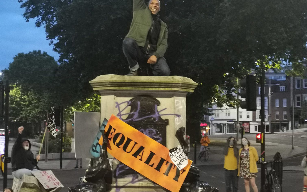 Photograph of a jubilant Black man kneeling on a statue plinth, with a raised right fist. The plinth is surrounded by placards reading 'EQUALITY', 'THE UK IS NOT INNOCENT' and 'BLACK LIVES MATTER'.