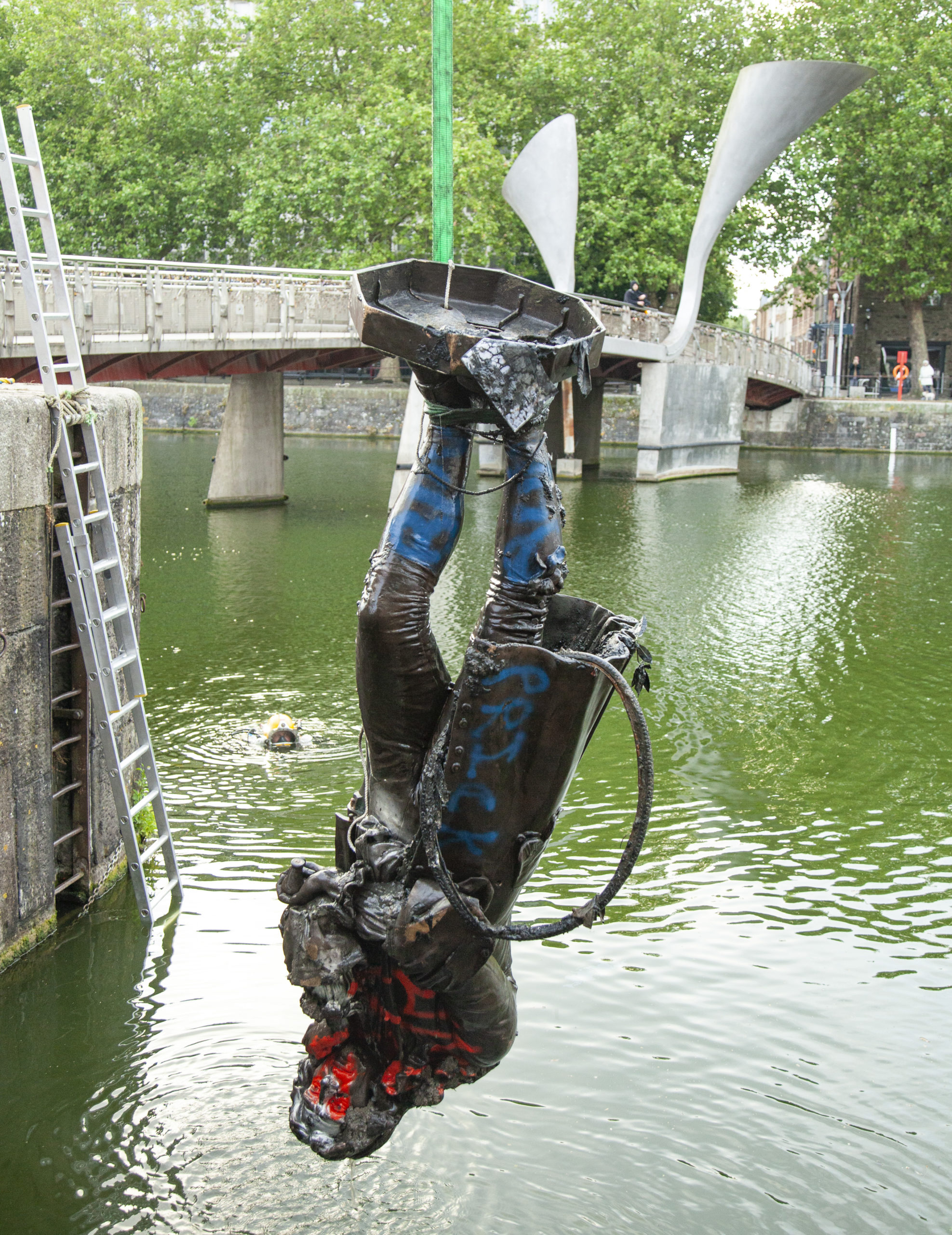 Colston statue hanging upside down, being brought up from Bristol harbour. It is painted in blue and red paint and has a tyre attached. Bridge in the background. Image Caption: Colston statue being brought up from Bristol harbour (© Bristol City Council)