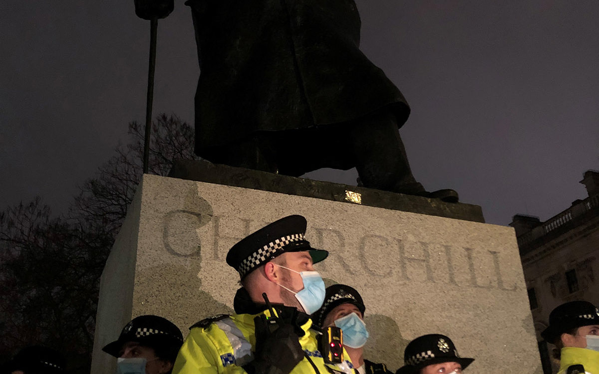 Statue of Winston Churchill, guarded by police in high vis jackets.