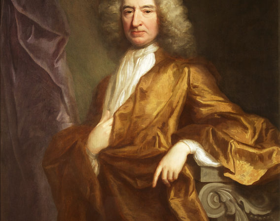 Portrait of Edward Colston. Painting of a man, looking at the viewer. He wears a loose bronze coloured robe, over a white shirt and long white necktie. His hair/ wig is long and grey. His left lower arm rests on a wooden rest. His right hand rests on his body, above the stomach, tucked into the fabric slightly. There is a dark background and a purple drape to the left of the painting.