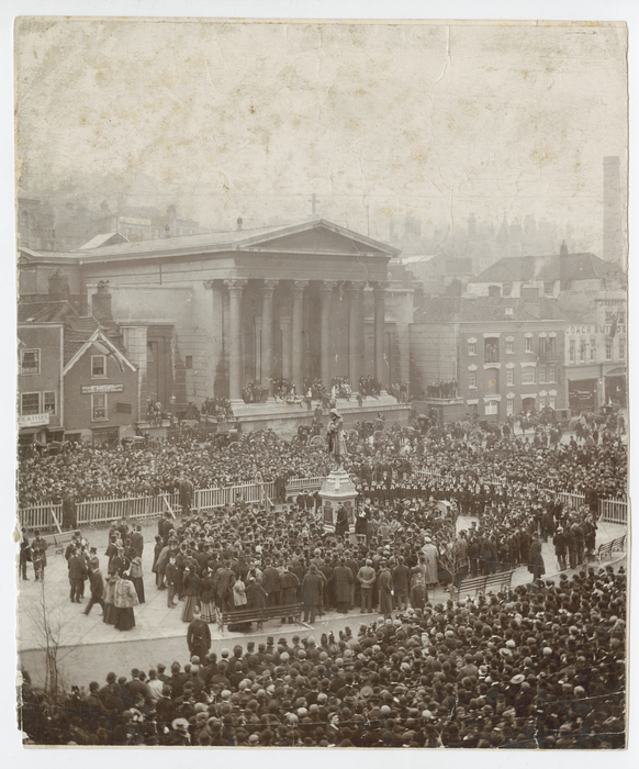 Sepia image of the opening ceremony of the statue of Colston. Large crowd of people surround the statue, with some areas barriered off.