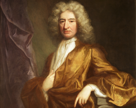 Portrait of Edward Colston. Painting of a man, looking at the viewer. He wears a loose bronze coloured robe, over a white shirt and long white necktie. His hair/ wig is long and grey. His left lower arm rests on a wooden rest. His right hand rests on his body, above the stomach, tucked into the fabric slightly. There is a dark background and a purple drape to the left of the painting. Edward Colston by Jonathan Richardson, c.1700 (© Bristol City Council)