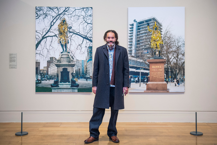 Artist Hew Locke stands between two of his large scale photographic artworks at 'Artist and Empire' Tate Britain exhibition, London, UK. 23 November 2015. On the left of the picture is a photo of the statue of Colston draped in gold embellishments. On the right of the picture is a photo of the statue of Burke draped in gold embellishments. (© Guy Bell/ Alamy Live News)