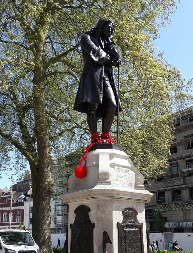 Edward Colston statue with a red woollen ball and chain added. Image caption: Knitted shackles are added to the statue (© Faith M)