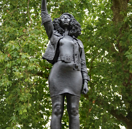 Black resin statue of a woman with her right hand held in a fist above her head. Trees in the background.