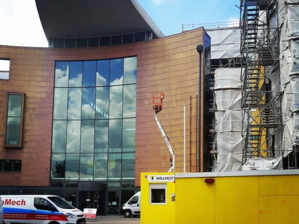 Building with scaffolding to the right, and a van parked outside. There are bright yellow building hoardings and a cherry picker. The building's sign has been removed.