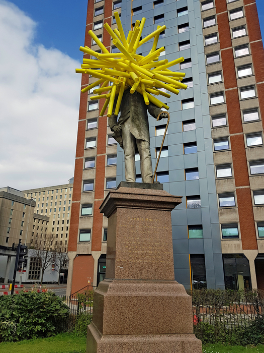 Statue of a man with a walking stick, in an urban area. The statue's head is covered in bright yellow foam tubes, in a roughly spherical shape.