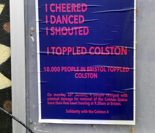 Blue poster with bright pink writing, on a noticeboard, behind cracked glass. 'I CHEERED/ I DANCED/ I SHOUTED/ I TOPPLED COLSTON'/ 10,000 PEOPLE IN BRISTOL TOPPLED COLSTON/ On Monday 25th January, 4 people charged with criminal damage for removal of the Colston Statue have their first court hearing at 9.30am at Bristol./ Solidarity with the Colston 4'.