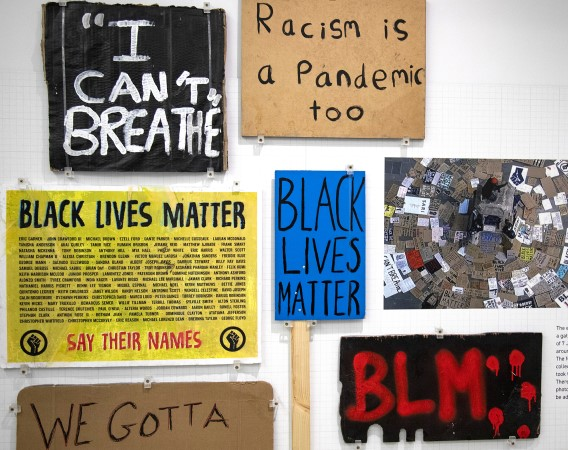 Photo of various placards from Black Lives Matter protest. It reads from the top left: card one black background and white painted text