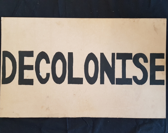 Placard with words 'Decolonise' in black text. (© Bristol Museums)