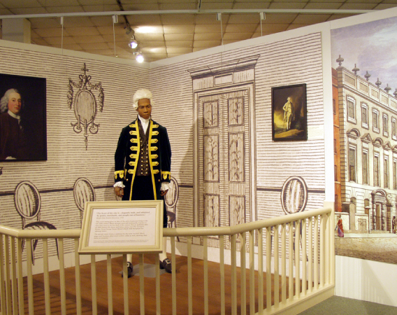Museum display showing a Black mannequin in a white wig. Graphics imply he is in a home, acting as a servant in Georgian Britain. Bristol & Transatlantic Slavery display at Bristol Industrial Museum. (© Bristol Culture, M Shed)